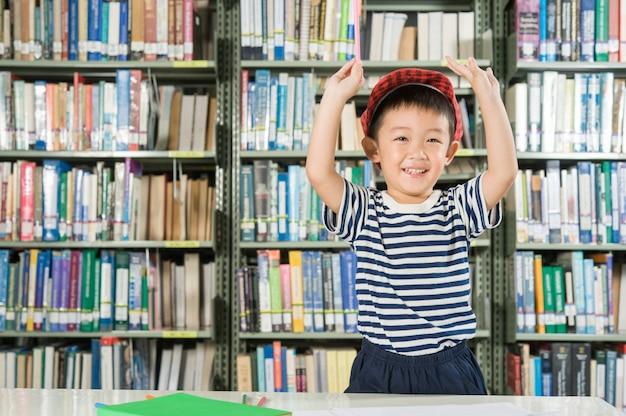 Menino asiático na escola da sala da biblioteca