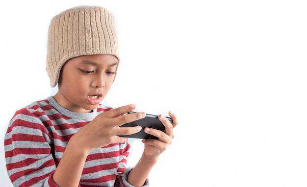 Menino asiático no chapéu de lã usando telefone inteligente em branco