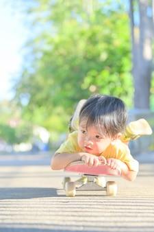 Menino asiático no skate. o menino aprende a andar de skate Foto Premium