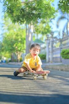Menino asiático no skate. o menino aprende a andar de skate