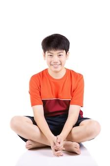 Menino asiático novo do retrato que senta-se sobre o fundo branco,