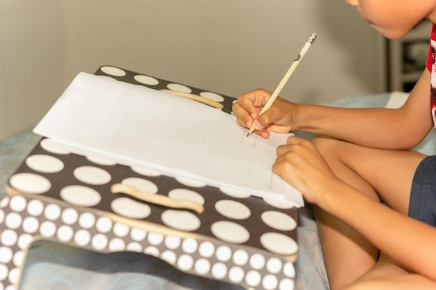 Menino asiático novo que faz seus trabalhos de casa em uma cama.