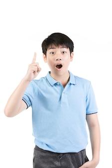 Menino asiático novo que pensa e que aponta para cima ao sorrir.