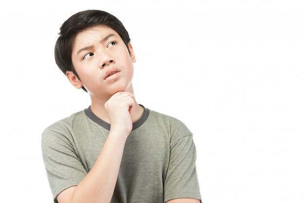 Menino asiático novo que pensa e que olha para cima ao sorrir.