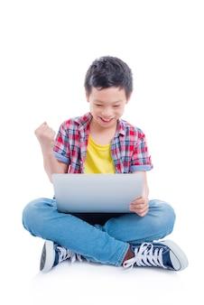 Menino asiático novo que senta-se no assoalho e que joga jogos no laptop sobre o fundo branco