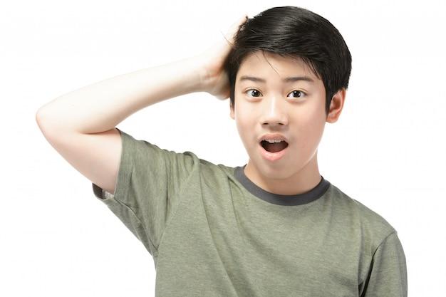 Menino asiático pequeno com cabelo preto em agir engraçado que tenta divertir-se.
