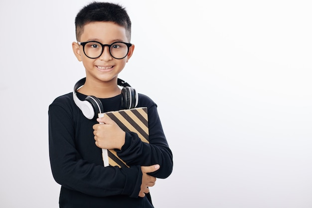 Menino asiático positivo de óculos segurando um livro e sorrindo, isolado no branco