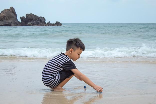 Menino asiático que joga o brinquedo em uma praia do mar.