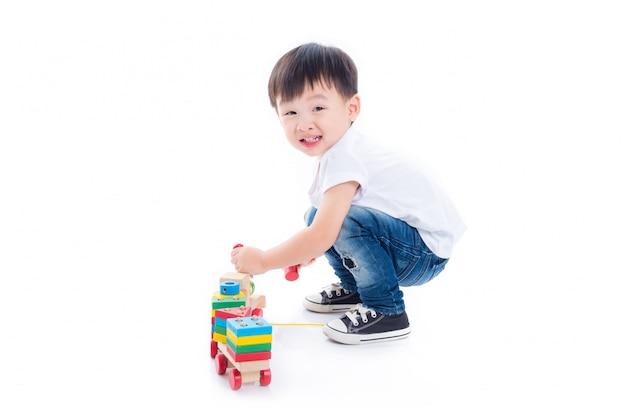 Menino asiático que joga o brinquedo no assoalho sobre o fundo branco
