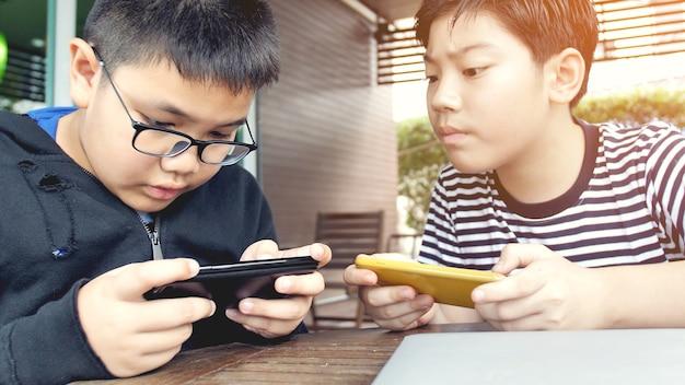 Menino asiático que joga o jogo móvel no telefone esperto junto.