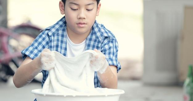Menino asiático que lava sua toalha à mão.
