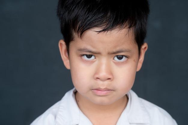 Menino asiático que mostra a frustração e irritado, isolado no fundo preto.