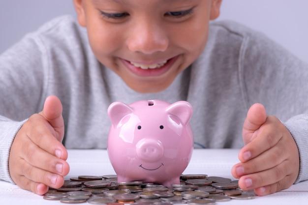 Menino asiático que olha ao mealheiro e às várias moedas. salvando o conceito de dinheiro.