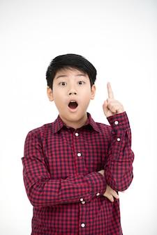 Menino asiático que sorri e que aponta o dedo acima.