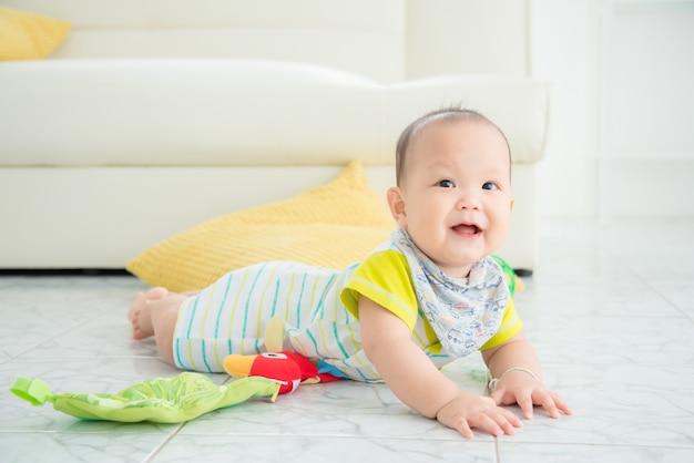 Menino asiático, rastejando no chão e sorrisos