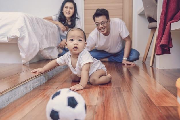 Menino asiático rastejar no chão de madeira sobre o pai e a mãe no quarto