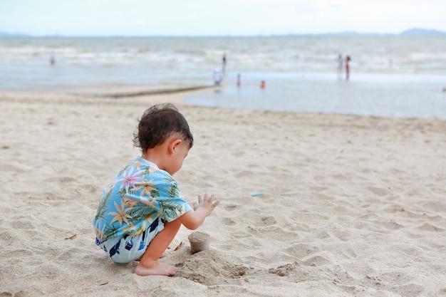 Menino asiático se divertindo com a areia na praia