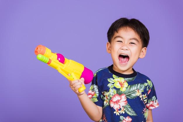 Menino asiático segurando uma pistola d'água de plástico, garoto tailandês engraçado segurando uma pistola d'água de brinquedo e sorrindo