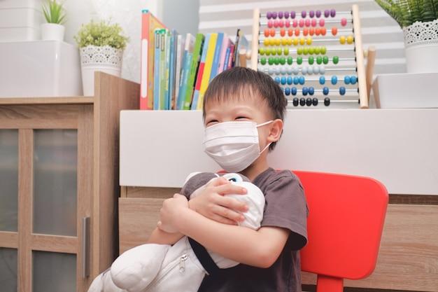 Menino asiático sorridente e feliz do jardim de infância abraçando seu brinquedo de pelúcia de cachorro com máscaras médicas protetoras