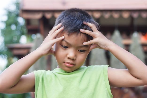 Menino asiático sozinho sente-se triste, com dor de cabeça e estressado.