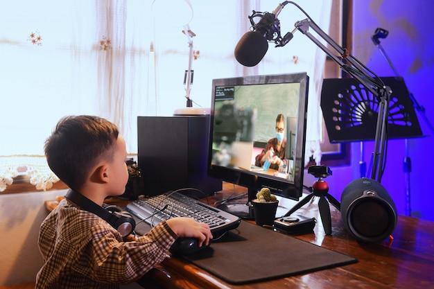 Menino asiático usando computador pc para estudar. foco selecionado na infância com fundo desfocado, estilo vintage