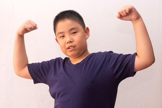 Menino asiático vestindo camiseta mostra quão forte e poderoso