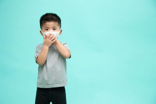 Menino asiático vestindo uma máscara protetora para coronavírus da peste ou doença infecciosa covid-19. máscara higiênica facial para conscientização ambiental ao ar livre de segurança ou conceito de propagação de vírus