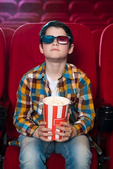 Menino assistindo filme no cinema