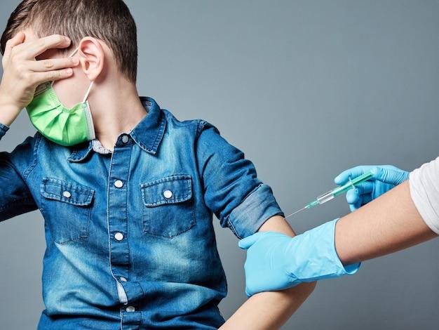 Menino assustado sendo vacinado isolado em cinza, conceito de vacinação