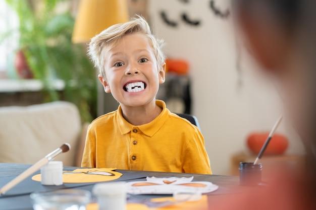 Menino assustador com presas brancas olhando para a câmera perto da mesa