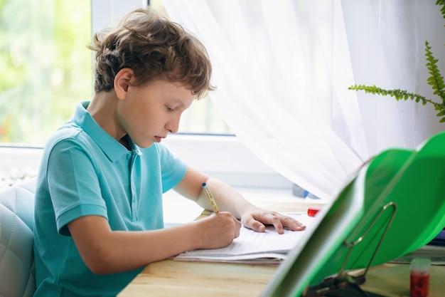 Menino atento, escrevendo no caderno enquanto está sentado na mesa e fazendo lição de casa.