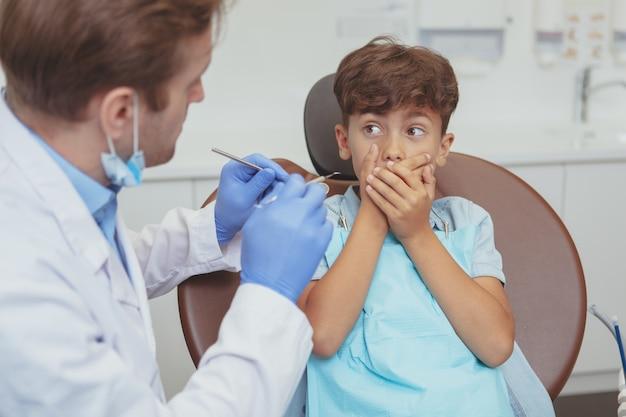 Menino aterrorizado, cobrindo a boca com as mãos, sentado em uma cadeira odontológica