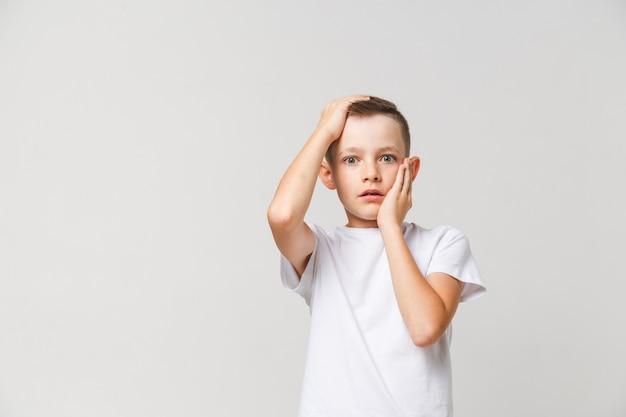Menino aterrorizado em t-shirt branca com as duas mãos na cabeça em fundo cinza