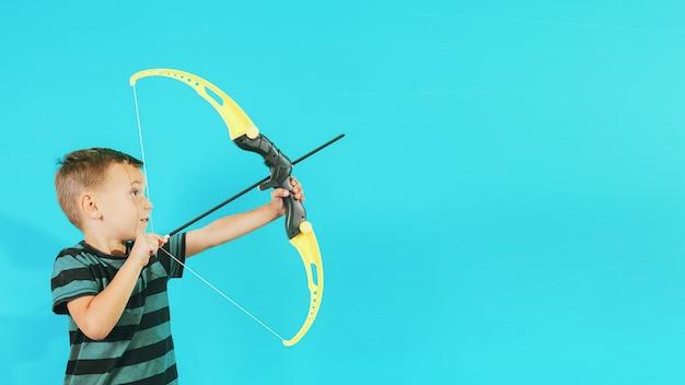 Menino atira um arco em um alvo na parede azul