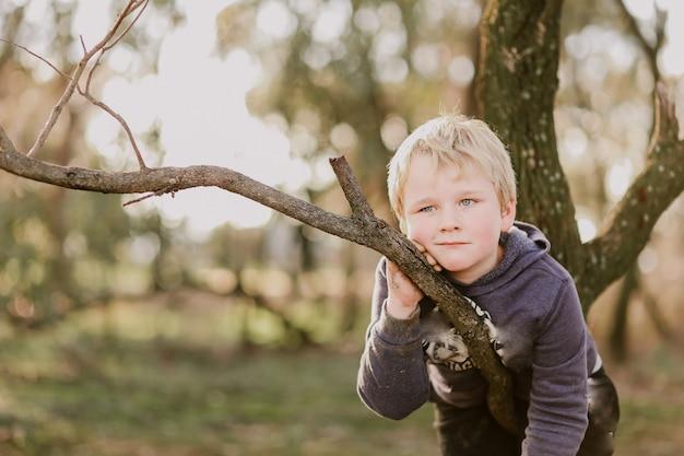 Menino australiano apoiado em um galho de árvore