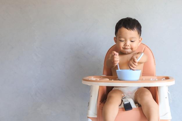 Menino bebê asiático infantil feliz sentado na cadeira alta de bebê e comendo comida sozinho com espaço de cópia.