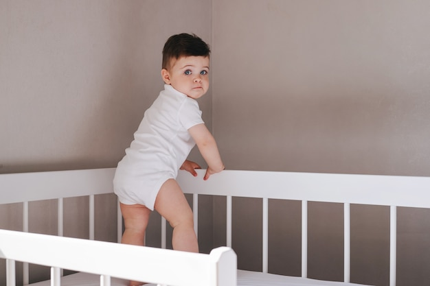 Menino bebê sentado na cama no quarto em um macacão branco