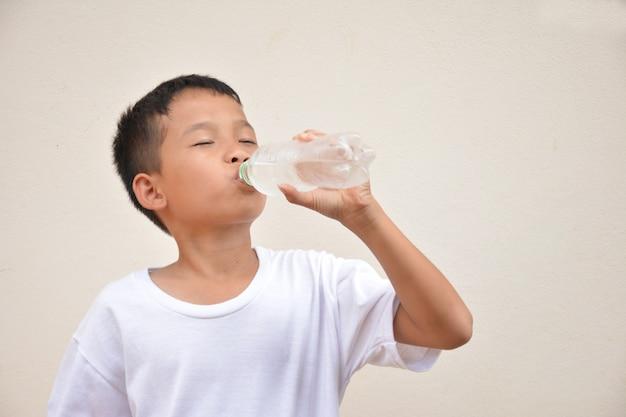 Menino bebendo água fundo cinza de cimento