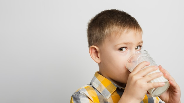 Menino bebendo leite com copo