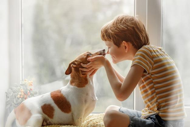 Menino beija o cachorro no nariz na janela.