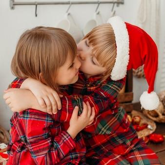 Menino beijando a irmã na bochecha
