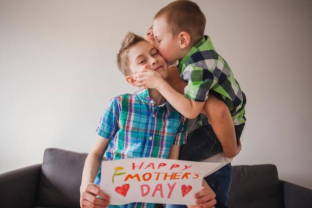 Menino, beijando, seu, irmão, mãe, dia
