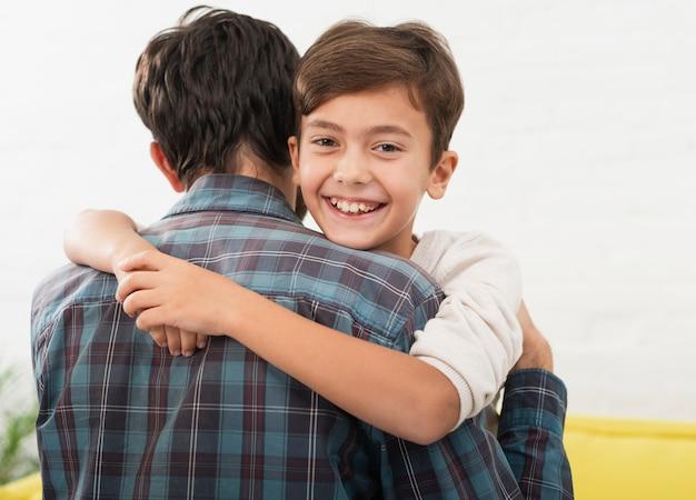 Menino bonitinho abraçando seu pai