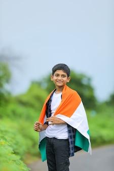 Menino bonitinho acenando a bandeira tricolor nacional indiana sobre o fundo da natureza