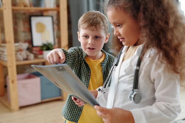 Menino bonitinho apontando para a imagem de raio-x enquanto brincava de médico com um amigo