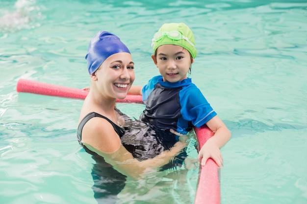 Menino bonitinho aprendendo a nadar com o treinador