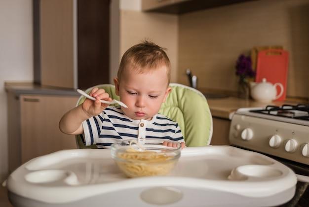 Menino bonitinho aprender a comer sozinho com um garfo. bebê come espaguete sentado em uma cadeira alta na cozinha.