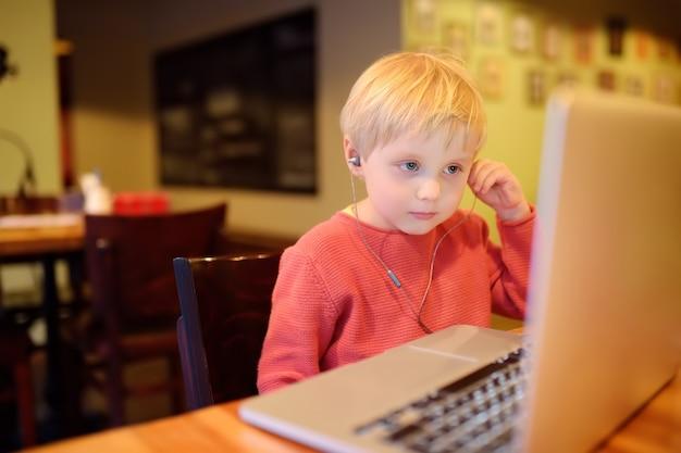 Menino bonitinho assistindo filme de desenho animado, usando o computador no café ou restaurante