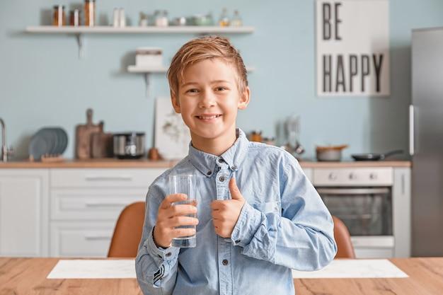 Menino bonitinho bebendo água na cozinha