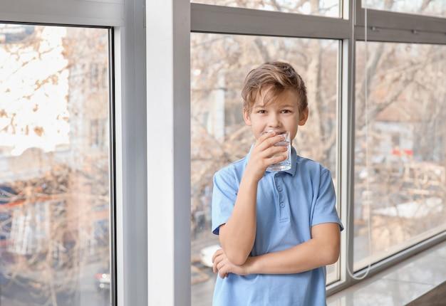 Menino bonitinho bebendo água perto da janela